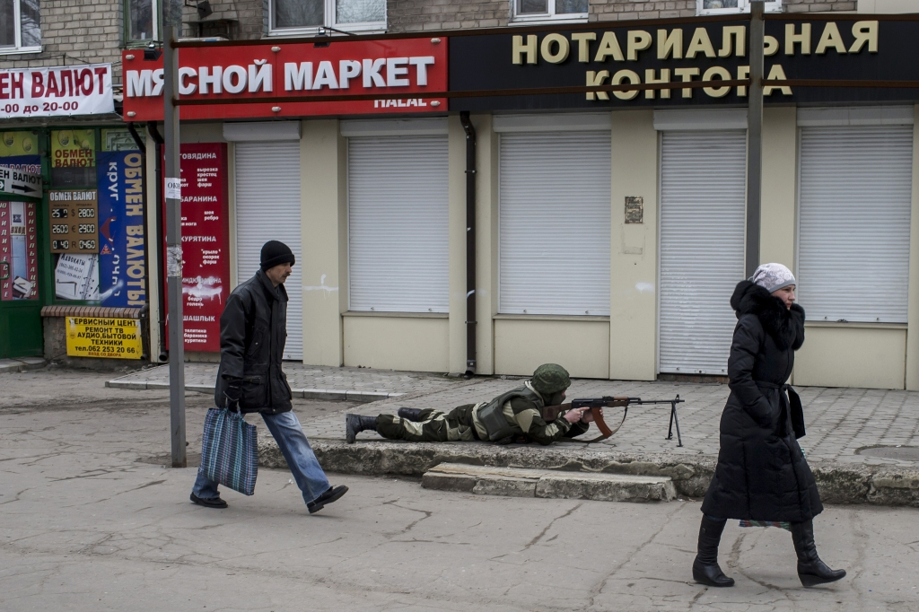 A pro Russian rebel aims his weapon as people pass by during what the rebels said was an anti-terrorist drill in Donetsk