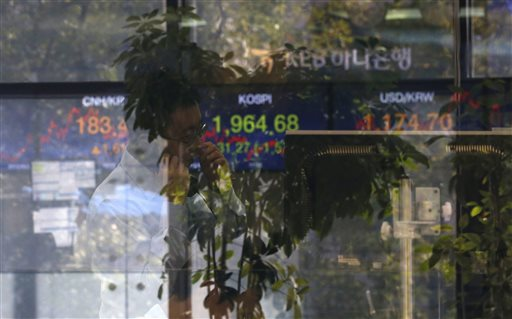 A currency trader talks on the phone near the screen showing the Korea Composite Stock Price Index at the foreign exchange dealing room in Seoul South Korea Monday Sept. 21 2015. Asian stock markets were mostly lower Monday after concerns abou