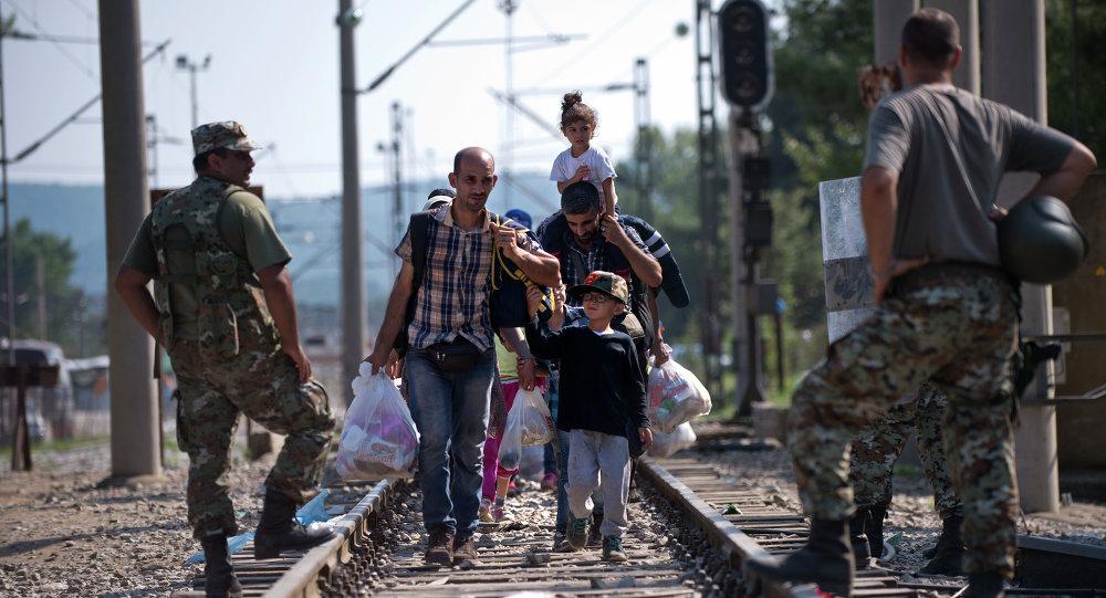 Migrants and refugees cross the Macedonian Greek border near Gevgelija