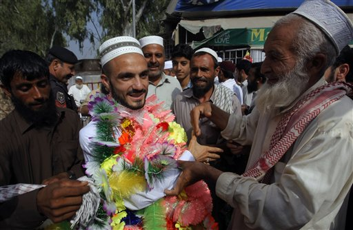 A Pakistani man center left is greeted by relatives on his arrival from Saudi Arabia after performing the Muslim hajj pilgrimage Monday Sept. 28 2015 in Peshawar Pakistan. Pakistan's minister for religious affairs says authorities have tracked