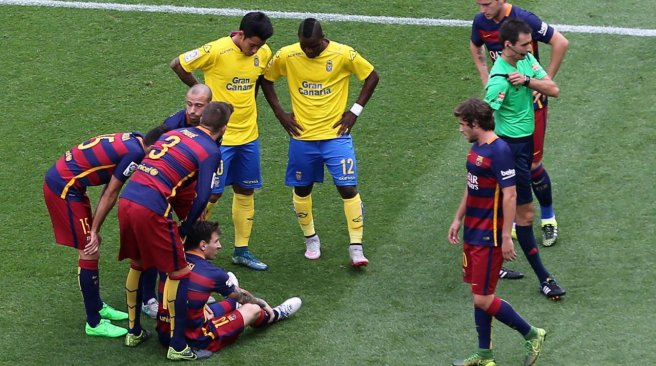 Barcelona forward Lionel Messi is surrounded by other players after being injured during the Spanish league football match FC Barcelona v UD Las Palmas at the Camp Nou stadium in Barcelona