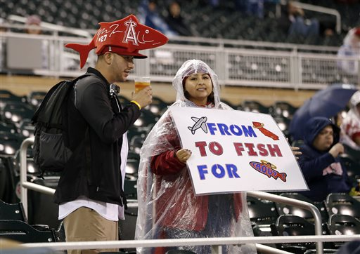 Fans of Los Angeles Angels&#039 Mike Trout wait during a rain delay prior to a baseball game between the Angels and Minnesota Twins Friday Sept. 18 2015 in Minneapolis