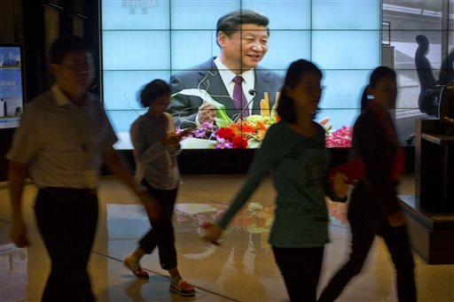 People walk past a large videoscreen showing Chinese President Xi Jinping during his trip to the United States from Chinese state broadcaster CCTV in an office building in Beijing Friday Sept. 25 2015. State media characterize Xis first state visit
