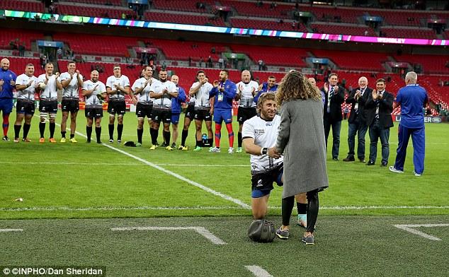 With his Romania team-mates gathered behind him Florin Surugiu asks his girlfriend to marry him at Wembley