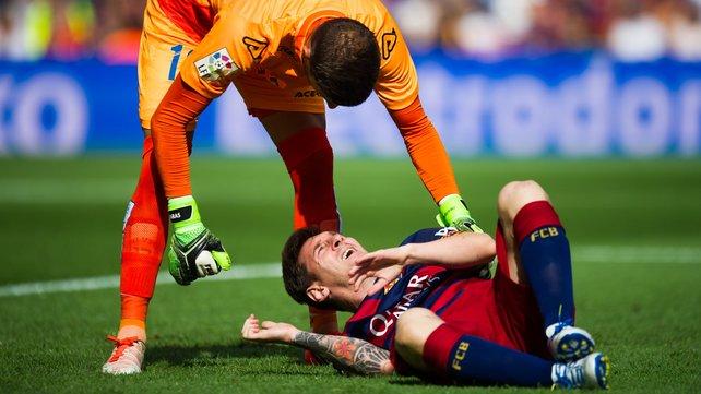 Javi Varas of UD Las Palmas helps the injured Lionel Messi