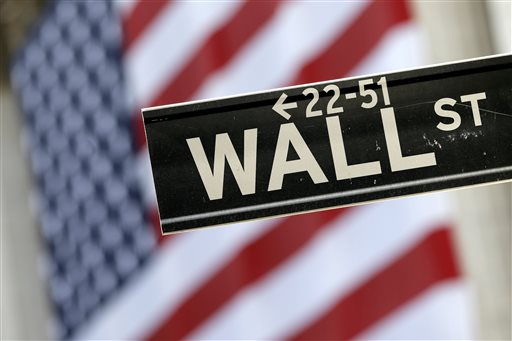 Wall Street street sign is framed by a giant American flag hanging on the facade of the New York Stock Exchange. European stock markets recovered their poise Tuesday Sept. 29 2015 despite an earlier rout in A