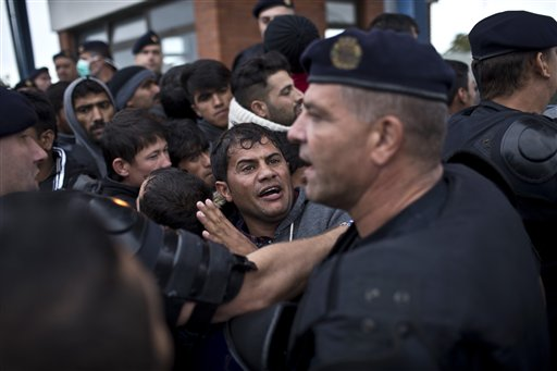 A man reacts as he gets pushed back by Croatian police officers in Opatovac Croatia Tuesday Sept. 22 2015. Scuffles have broken out between Croatian police and asylum-seekers after they were barred from entering a newly opened reception center meant