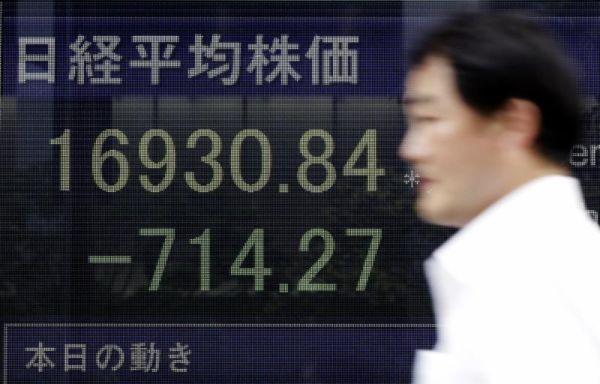 A man walks past an electronic stock board