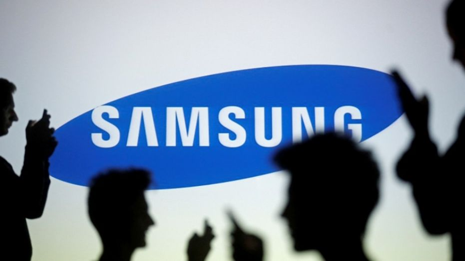 People are silhouetted as they pose with mobile devices in front of a screen projected with a Samsung logo in this